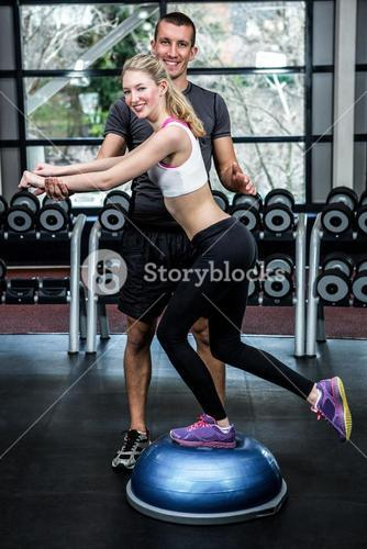 Fit woman with trainer exercising with bosu