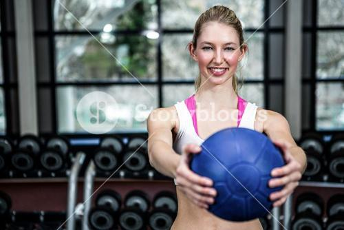Smiling fit woman exercising with medicine ball