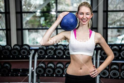 Fit woman with hand on hip holding medicine ball