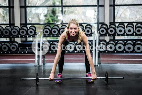 Smiling fit woman lifting barebell