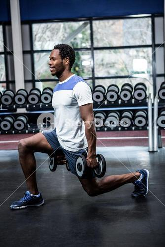 Smiling man exercising with dumbbells