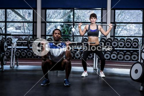 Fit couple exercising with barebell