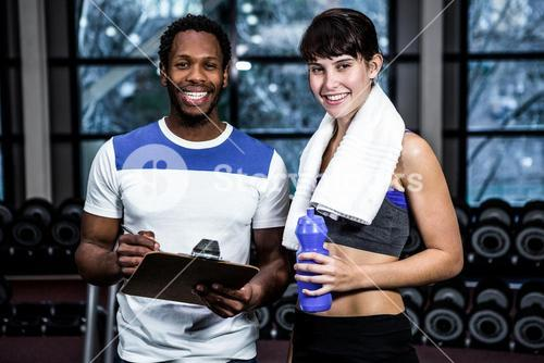 Male trainer and fit woman smiling