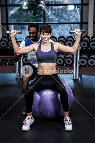 Male trainer helping woman during dumbbells exercise