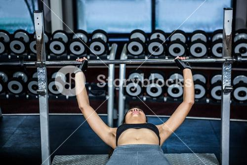 Fit woman lifting barbell while lying on bench