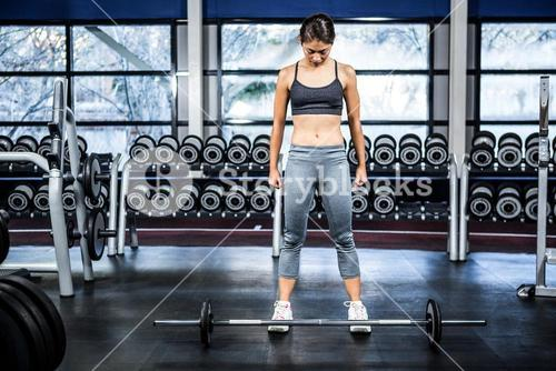 Fit woman preparing herself for barebell exercise