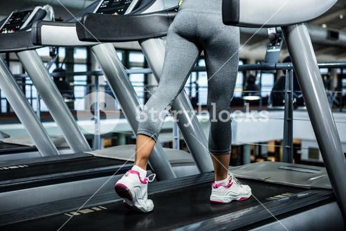 Mid section of woman using treadmill