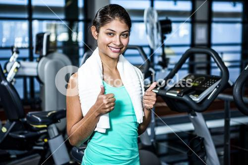 Smiling fit woman with thumbs up