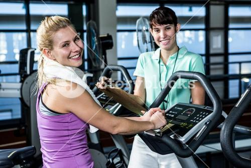 Fit woman doing exercise bike with trainer