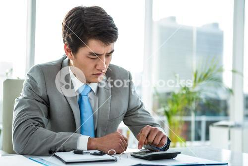 Troubled businessman using calculator