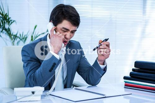 Angry asian businessman on the phone