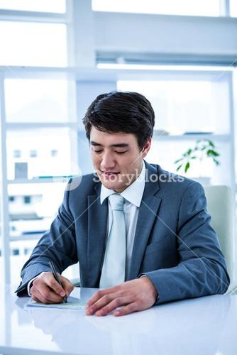 Smiling asian businessman completing a cheque