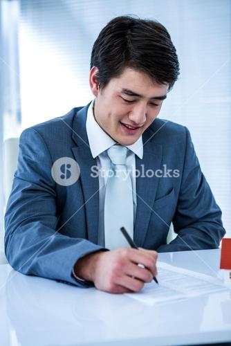 Smiling asian businessman read a estate contract