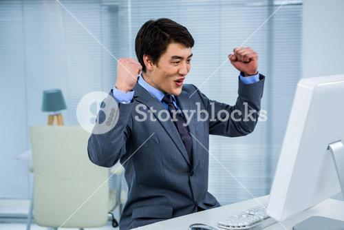 Businessman,celebrating with arms up