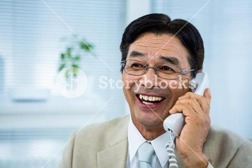 Smiling businessman talking on the telephone