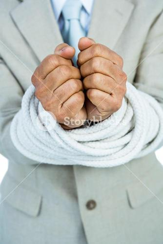 Businessman tied up in rope