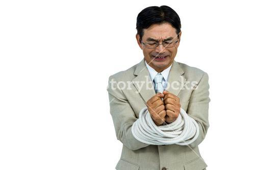 Asian businessman tied up in rope