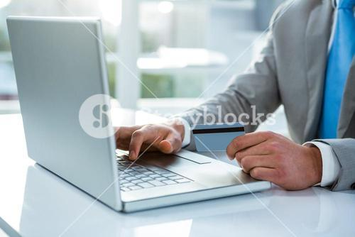Businessman holding his credit card to pay