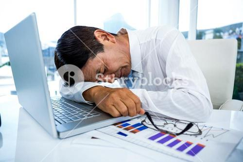 Exhausted businessman sleeping on his laptop