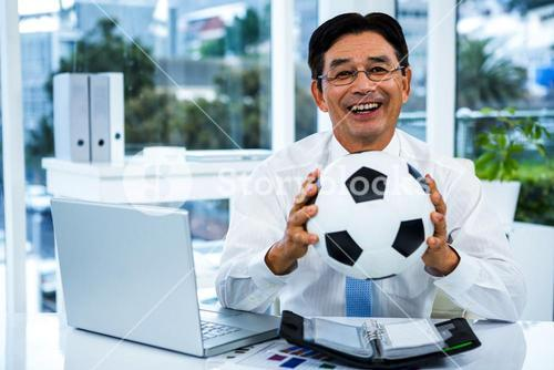 Asian businessman holding soccer ball