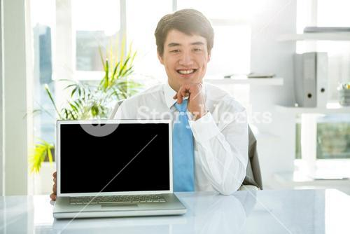 Smiling businessman showing his computer
