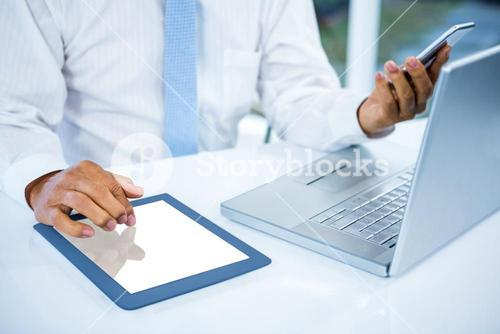 Businessman using tablet and phone