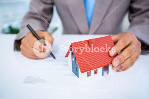 Businessman taking notes with miniature house
