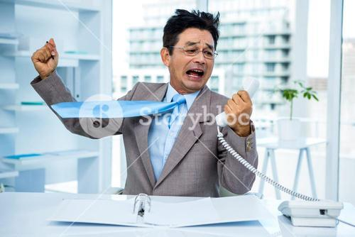 Businessman shouting as he holds out phone