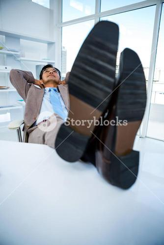 Successful businessman relaxing with his feet on his desk