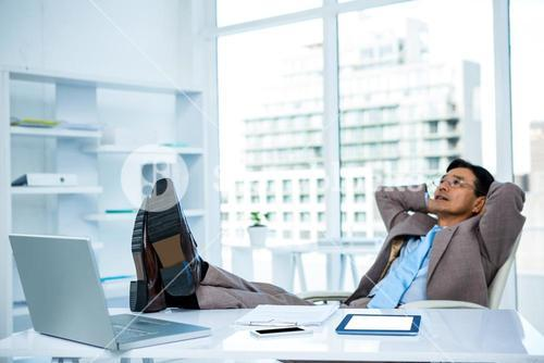 Businessman relaxing with his feet on his desk