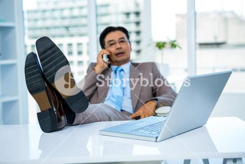 Businessman on the phone with his feet on his desk