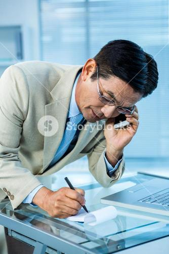 Overwhelmed asian businessman answering the phone and writing