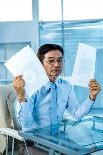 Busy businessman showing papers