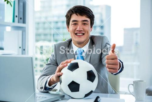 Asian businessman holding soccer ball with thumps up