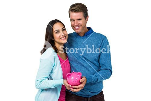 Smiling couple holding piggy bank