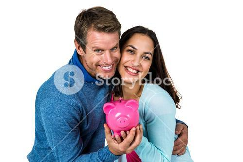 Smiling couple with pink piggy bank