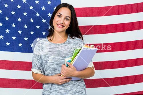 Portrait of smiling woman standing against American flag