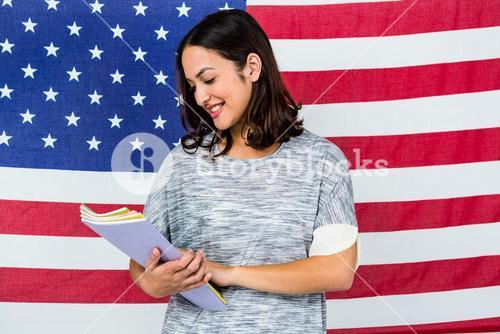 Smiling woman standing against American flag