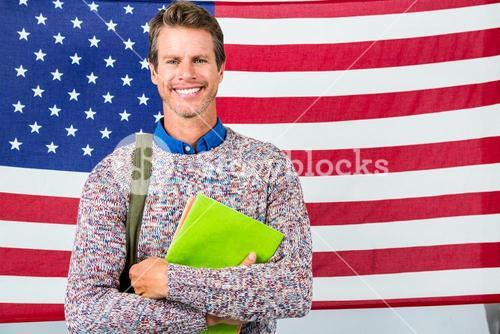 Smiling man standing against American flag