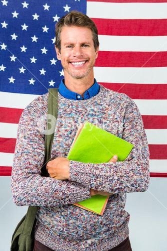 Portrait of happy man standing against American flag