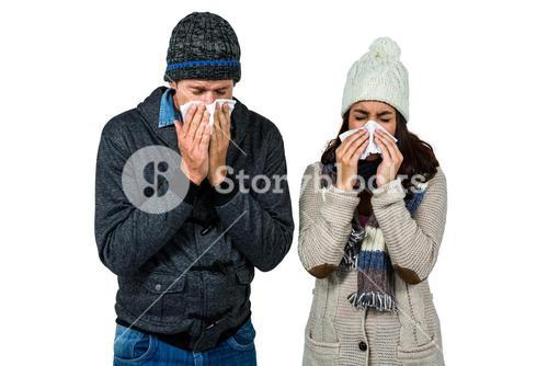 Winter couple blowing their noses