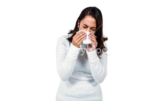 Woman sneezing while standing