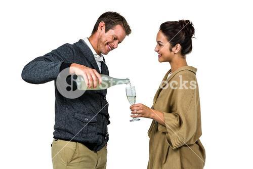 Smiling man pouring wine in glass with woman