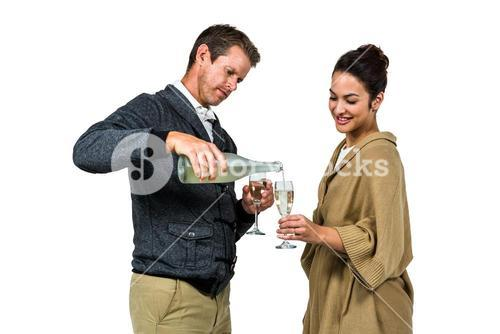 Man pouring wine in glass with smiling woman