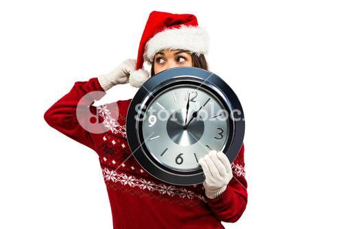 Festive brunette showing a clock