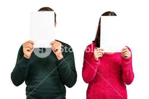 Couple hiding faces with documents