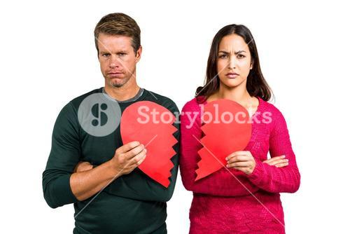 Portrait of serious couple holding cracked heart shape