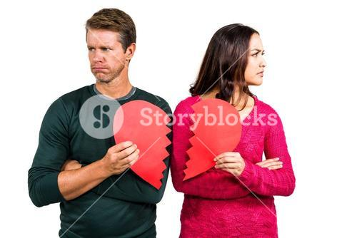 Serious couple holding cracked heart shape