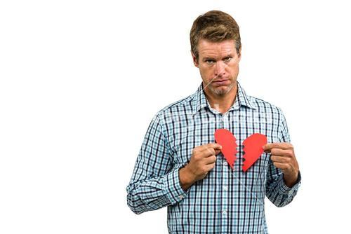 Portrait of sad man holding broken heart