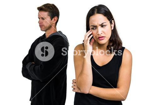 Depressed couple standing against white background